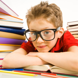 Smart youngster in eyeglasses putting his head on open book and looking at camera